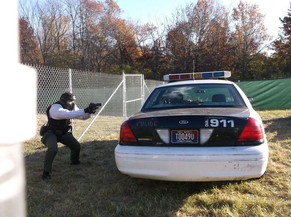 Non-Lethal Training Ammunition area, cadet behind a car