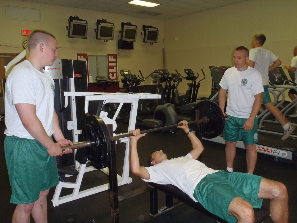 cadets bench pressing with spotters